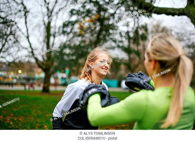 Female boxers training together in park