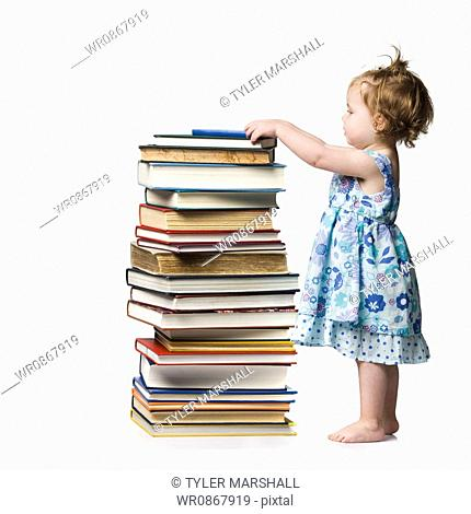 Young girl standing beside stack of hardcover books
