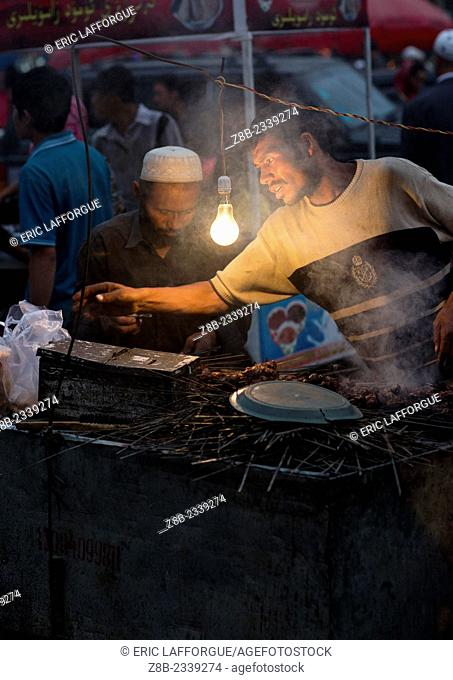 Uyghur Men Preparing Skewers In The Night Market, Hotan, Xinjiang Uyghur Autonomous Region, China