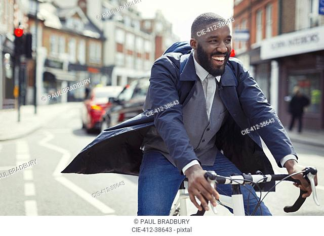 Smiling young businessman commuting, riding bicycle on sunny urban street