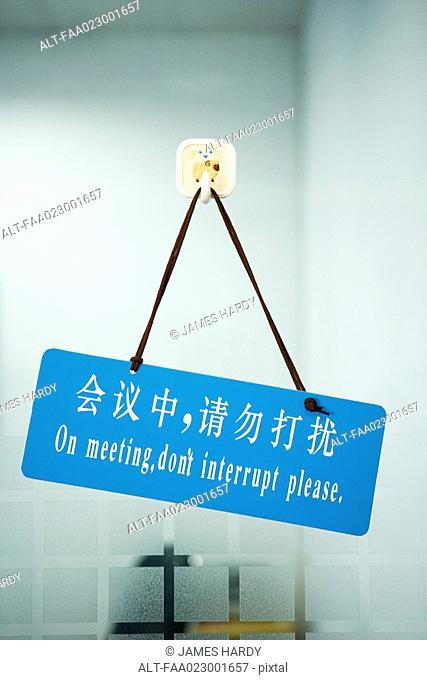 Bi-lingual sign on door stating 'On meeting, don't interrupt please,' in Chinese script and English