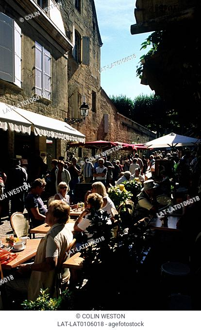 Medieval market town. Narrow street. Cafe tables and chairs. People seated,walking