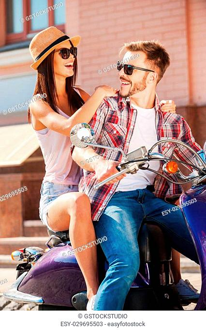 Enjoying their time together. Beautiful young couple sitting on scooter together while handsome man looking over shoulder and smiling