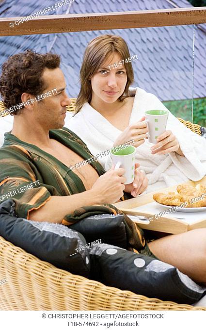 couple having breakfast on sofa