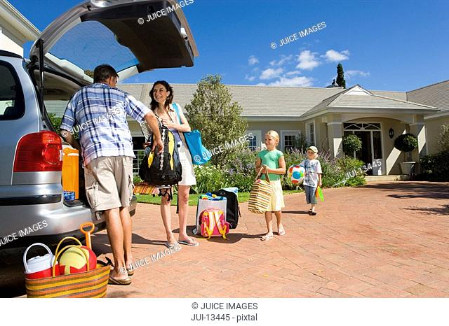 Family of four loading boot of car with luggage, low angle view
