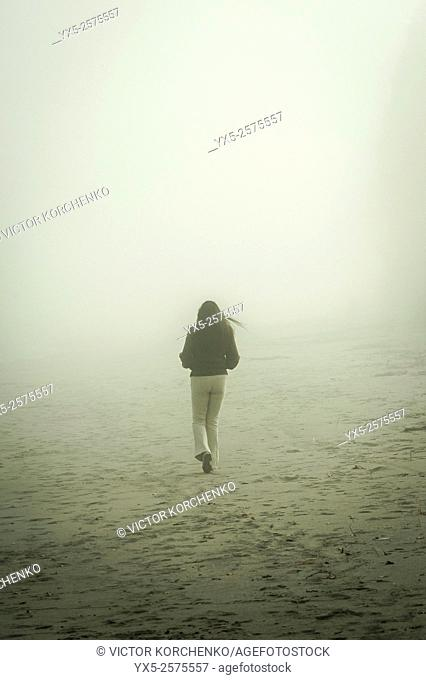 woman walking in the mist on a sandy beach
