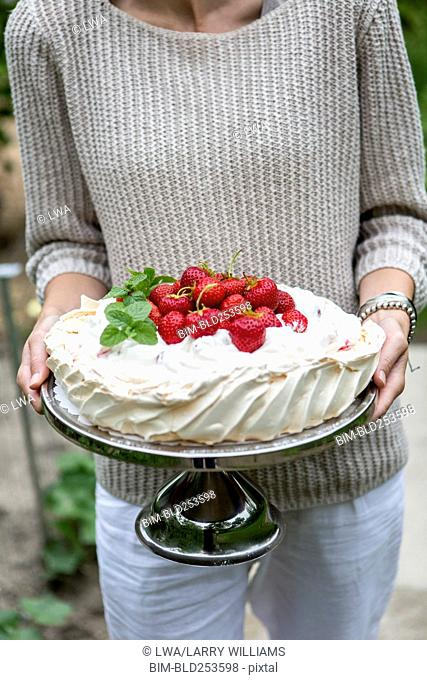 Woman carrying cake on tray with strawberries