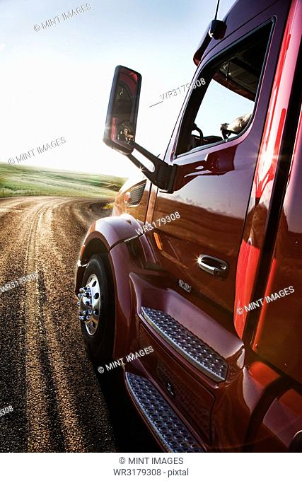 Close up side view looking forward of a commercial truck on a highway at sunset