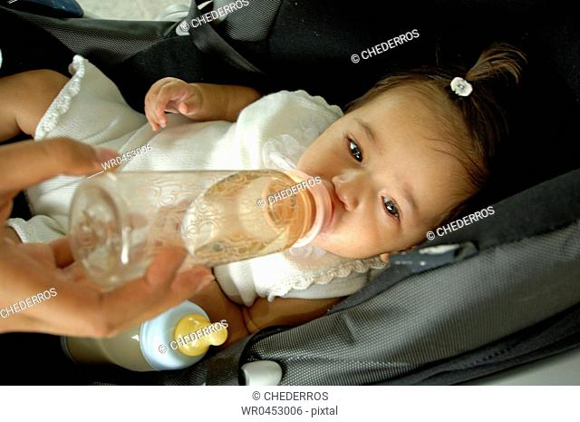 Close-up of a human hand feeding a baby girl with a baby bottle