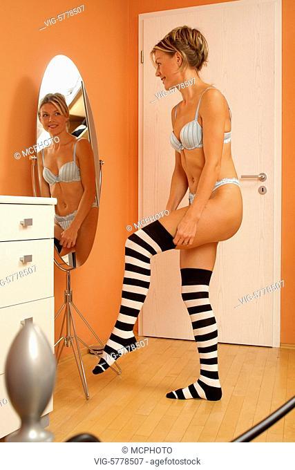 Eine Frau betrachtet ihre Figur im Spiegel, 2005 - Hamburg, Germany, 11/10/2005