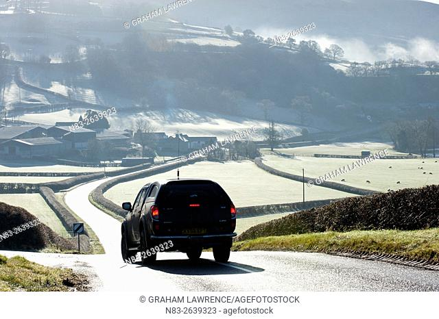 A motorist drives through a frosty landscape along the road between Aberedw and Builth Wells, Powys, UK