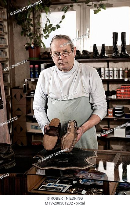 Cobbler in store holding pair of leather shoes
