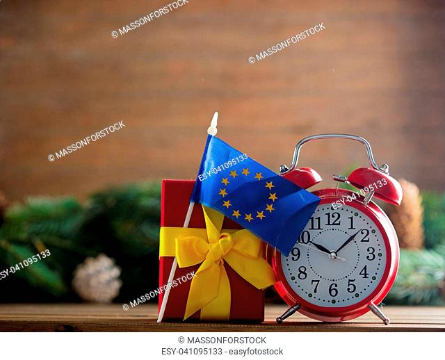 Red vintage alarm clock and gift box with Europe Union flag with pine tree branch and cones on background. Image in Christmas Holiday style