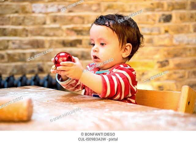 Baby boy playing with Christmas bauble at table