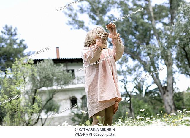 Little girl picking flowers on meadow