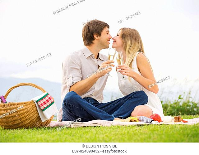 Attractive couple drinking champagne on romantic afternoon picnic in countryside