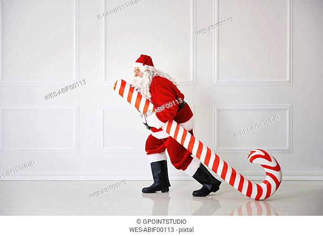 Santa Claus carrying oversized candy cane