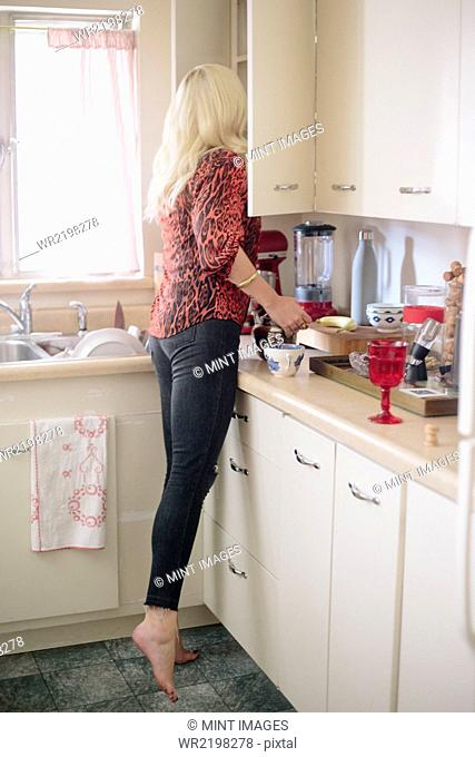 Blonde woman standing in a kitchen on tiptoes looking in a cupboard