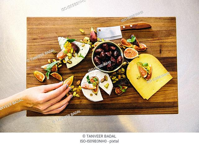 Variety cheese plate with figs, olives, pistachios, cleaver on wooden chopping board