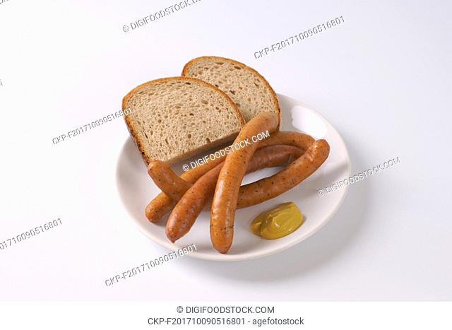 long thin sausages with slices of bread and mustard on white plate