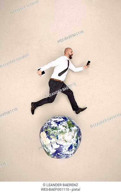 Businessman running on globe with mobile devices