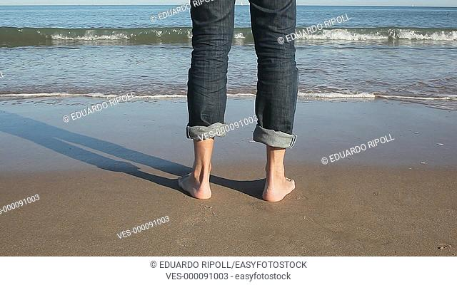 close up of bare feet standing in front of the beach