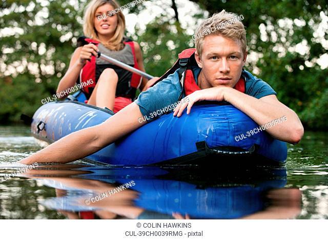 Man relaxing in kayak in creek
