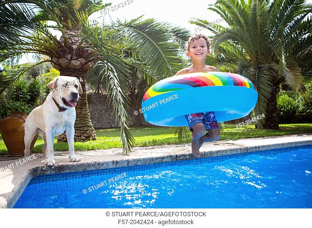 Young boy jumping into the pool with a large rubber ring