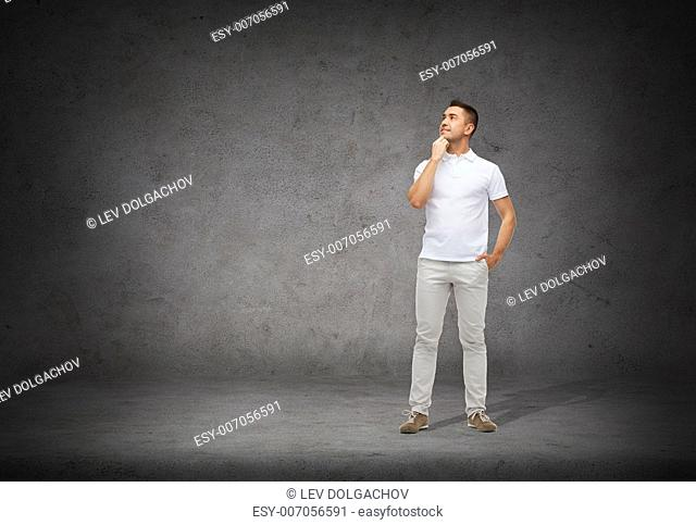 happiness and people concept - smiling man with hands in pockets looking up and thinking over concrete background