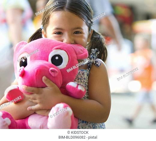 Young girl holding stuffed animal