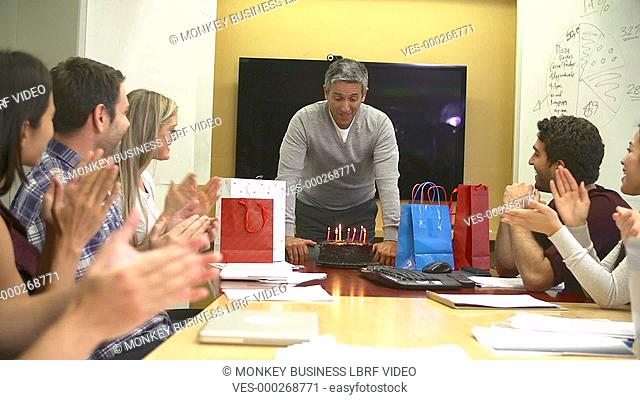Group of office workers presenting colleague with a birthday cake with candles which he blows out in slow motion .Shot on Sony FS700 in PAL format at a frame...