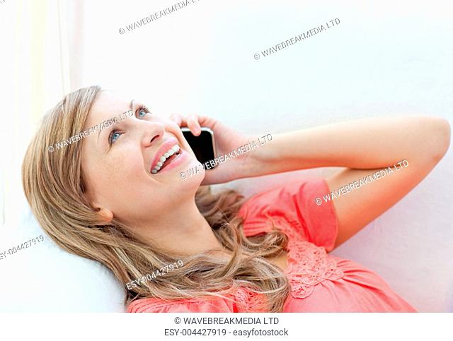 Jolly woman talking on phone lying on a sofa