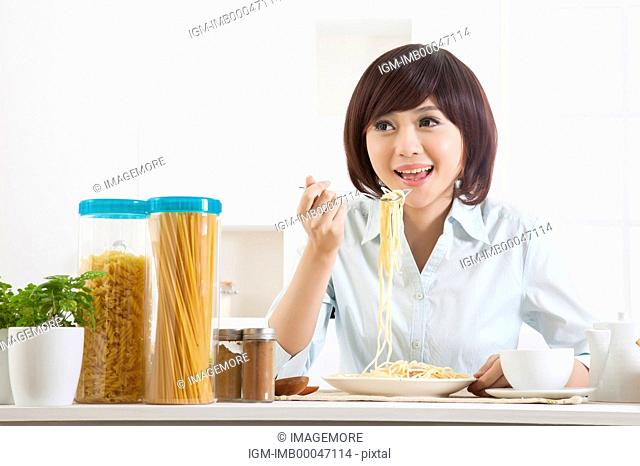 Young woman eating spaghetti and looking away with smile