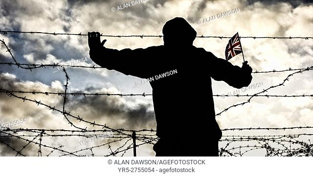 Rear view of man wearing hooded jacket holding Union Jack flag looking through razor wire fence. Immigration, borders, asylum, EU, Brexit.