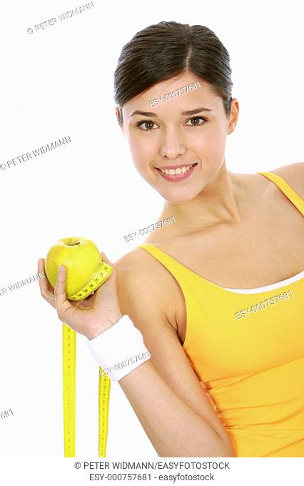 Fitness woman with green fresh apple and measuring tape