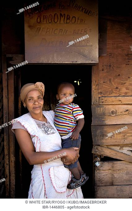 Woman with child in front of her beer bar in the Langa township, Cape Town, Western Cape, South Africa, Africa
