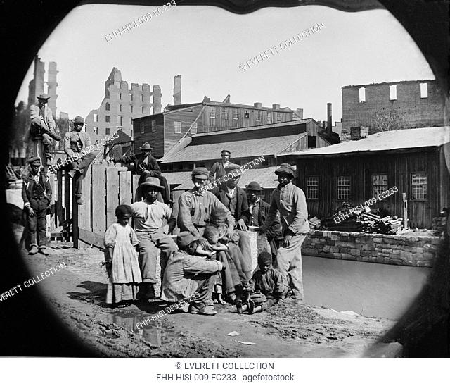 A newly freed African American group of men and a few children posing by a canal against the ruins of Richmond, Virginia