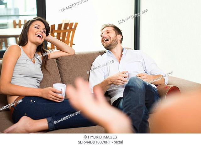 Couple having coffee together on sofa