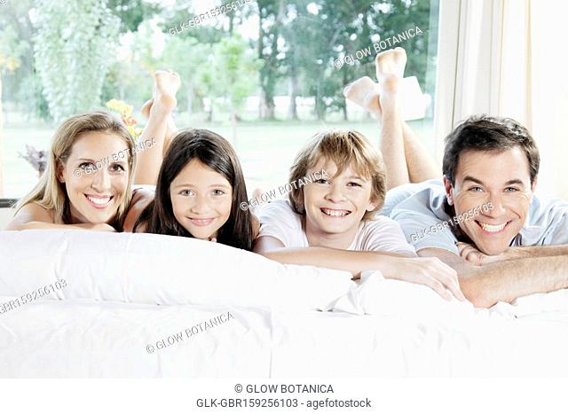 Family lying on the bed and smiling