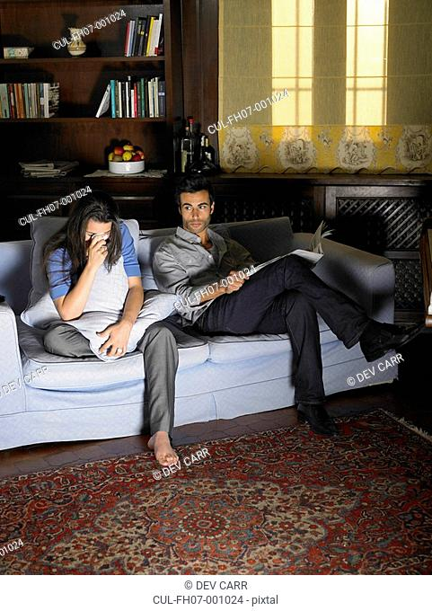 Young couple sitting on sofa illuminated by television, woman crying