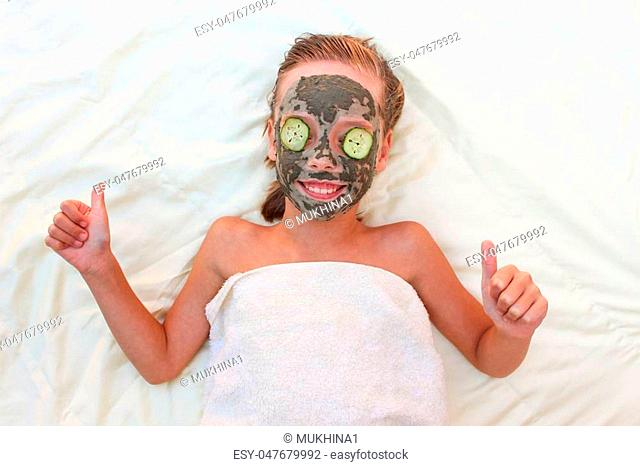 Beautiful girl with facial clay and cucumber mask