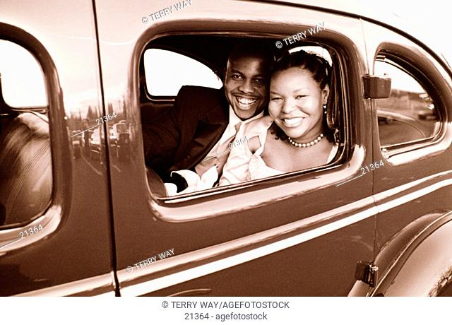 Just married and off in a vintage car in black and white