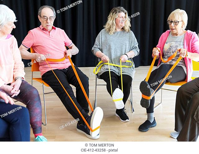 Active seniors exercising in circle, using straps to stretch legs