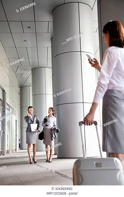 Three young businesswomen walking outside and talking on the phone