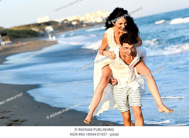 Young happy couple walking in a beautiful beach. Funny Man and woman wearing casual clothes. Male carrying his girlfriend in his arms