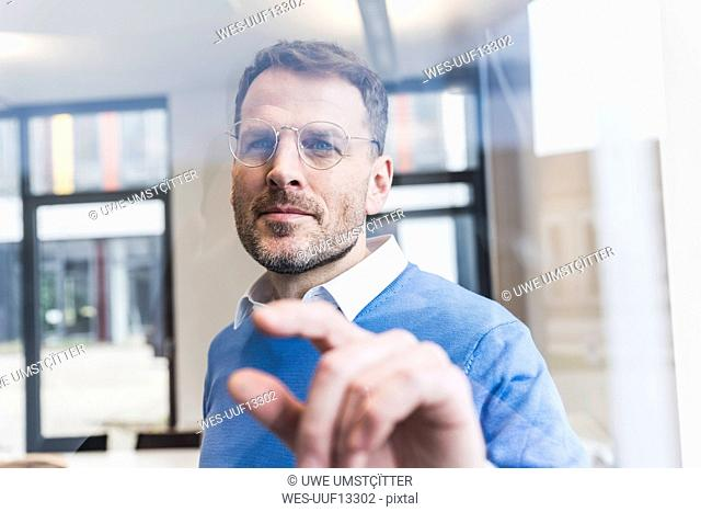 Confident businessman touching glass pane