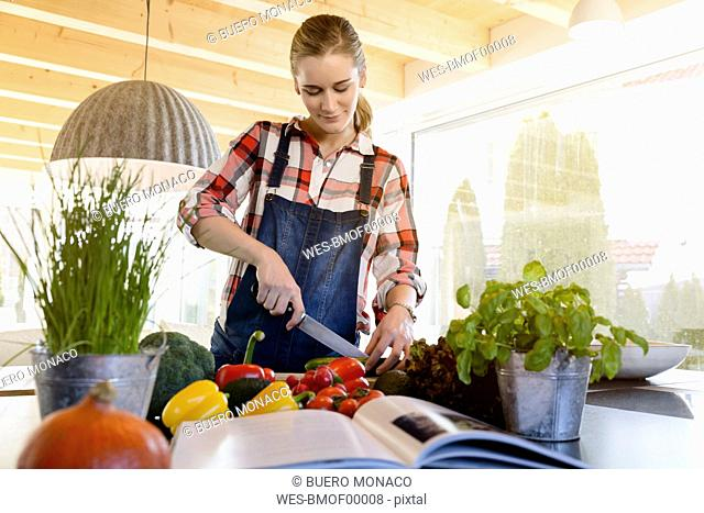 Pregnant woman in kitchen at home cutting cucumber