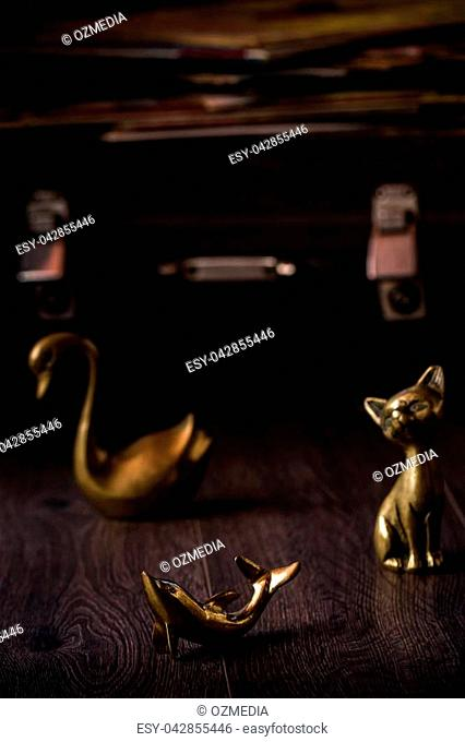 Vintage cat, dolphin and swan brass figurines on brown background