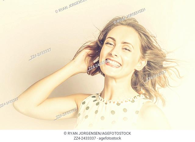 Vintage style beauty portrait of a luxury lady smiling with delight on sepia toned background. Retro fashion pin-up model