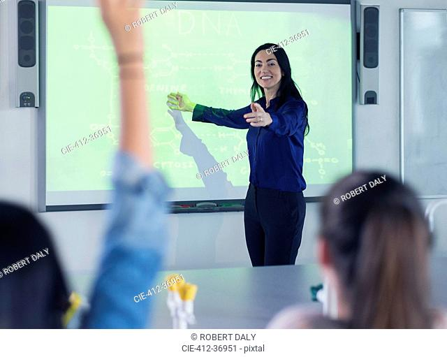 Smiling female science teacher leading lesson at projection screen in classroom